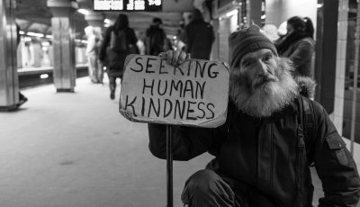 Man holding sign saying seeking human kindness