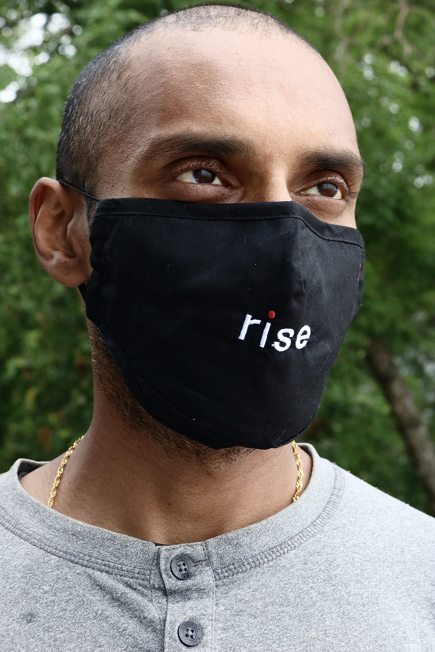 man wearing black mask with the word rise in white