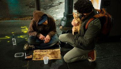 Person talking to homeless man with cat